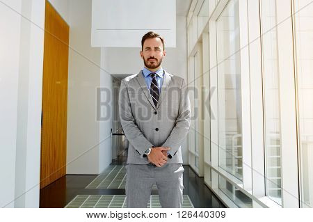 Confident man owner of big successful company dressed in expensive classic suit is waiting for his business partners. Young male intelligent CEO in formal wear is standing in modern office interior