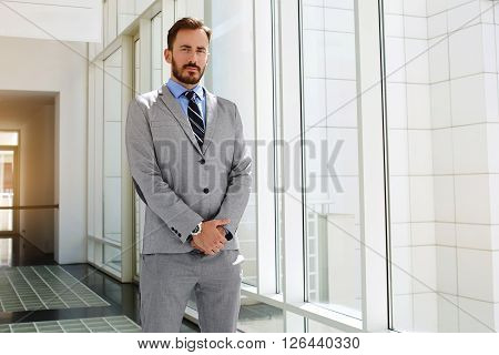 Young man jurist with serious face is posing after court hearing. Skilled male government worker in formal wear is resting after conference. Successful economist dressed in suit is looking at camera