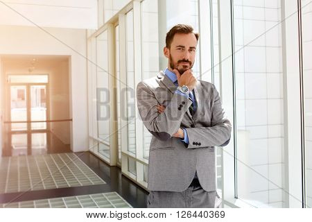 Young man professional architect with thoughtful face is standing in modern office interior during work break. Male entrepreneur is pondering about something before meeting with important customers