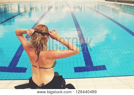 Swimmer taking a rest at the edge of a pool.