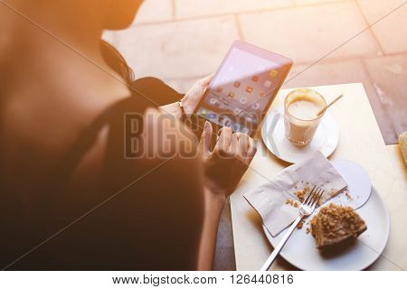 Closeup back view of young woman choosing application for start using her digital tablet during breakfast in cafe. Freelancer is connecting to coffee shop wireless via touch pad for browsing internet