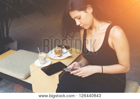 Attractive hipster girl is chatting with her friend on moile phone while is waiting for the order in cafe. Woman is searching information in network by using cell telephone during lunch in work break