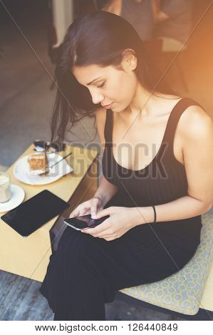 Attractive latin female typing text message while is chatting in network by mobile phone. Young woman during breakfast is using cell telephone for organize by application all things to do in the day