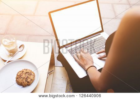 Rear view shot of woman's hands keyboarding for search information in internet by using net-book. Female person sitting front open laptop computer with blank mock up empty screen for your text message