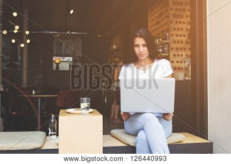 Young latin woman is sitting with open laptop in modern sidewalk coffee shop. Female freelancer is using net-book for distance work by internet connection.Student hipster girl is learning via computer