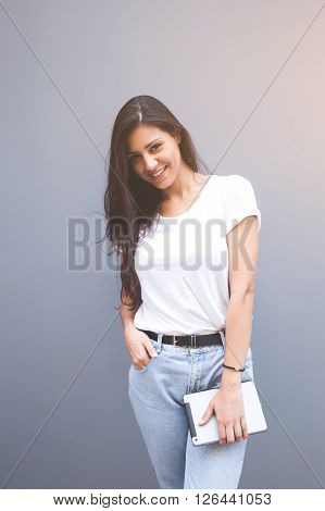Beautiful smiling latin woman dressed in mock up white clothing is holding her digital tablet while posing for the camera against copy space wall happy female with touch pad in hand looking at you