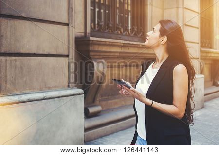Half length portrait of young woman tourist using touch pad for navigation while lost the way during walking female wanderer is using digital city map on her tablet computer during strolling outside