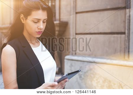 Half length portrait of latin business woman reading fashion news on touch pad while walking on the street modern female using digital tablet computer for navigation during strolling in urban setting