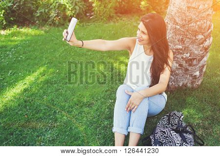 Young pretty woman is posing while photographing herself on cellphone for social network picture during recreation time in park charming latin female is making self portrait with mobile phone camera