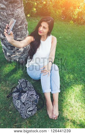 Portrait of attractive hipster girl is making self portrait with her smart phone digital camera young female posing while photographing herself for social network picture while resting after walking