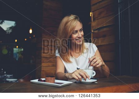 Young woman with beautiful smile looking away while sitting in cafe during coffee break happy charming hipster girl relaxing in modern cafe female enjoying good day during morning breakfast in bar