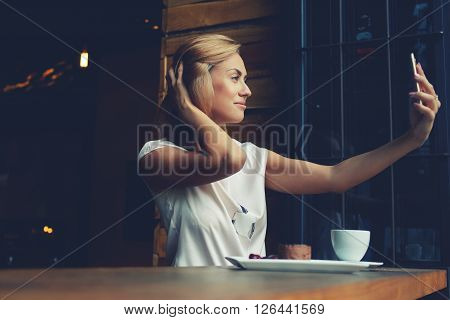 Young gorgeous woman making self portrait with mobile phone camera while sitting alone in modern coffee shop attractive European female posing while photographing herself for social network picture