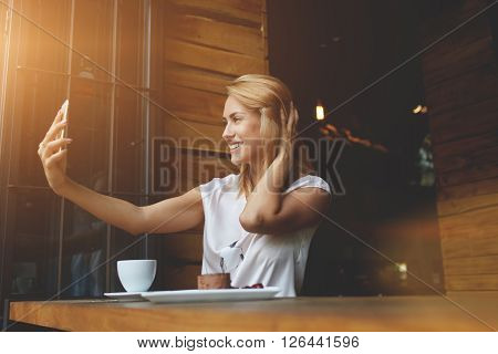 Young pretty woman with beautiful smile posing while photographing herself on mobile phone camera happy hipster girl making photo with cell telephone for a chat with friends while sitting in cafe