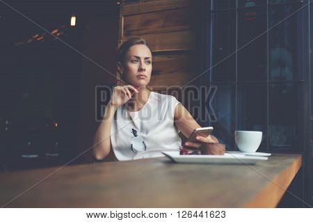 Young pensive woman dreaming about something while waiting for a call on her cell telephone beautiful thoughtful hipster girl using mobile phone while siting alone in modern coffee shop interior