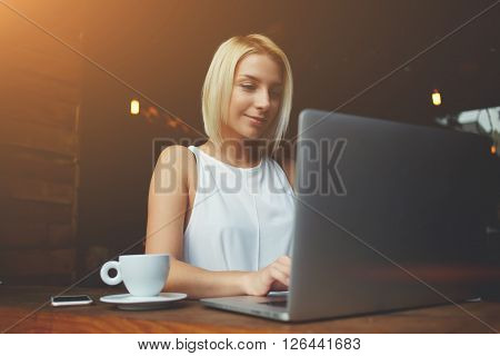 Pretty female student with cute face keyboarding text message on net-book while relaxing after lectures in University woman freelancer is working on laptop computer during breakfast in cafe bar