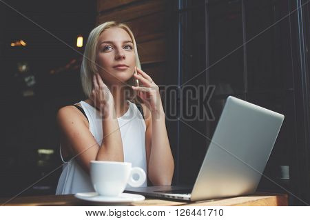 Gorgeous young woman talking on her smart phone while is sitting with portable net-book in coffee shop beautiful blonde female calling on cell telephone while rest after work on laptop computer