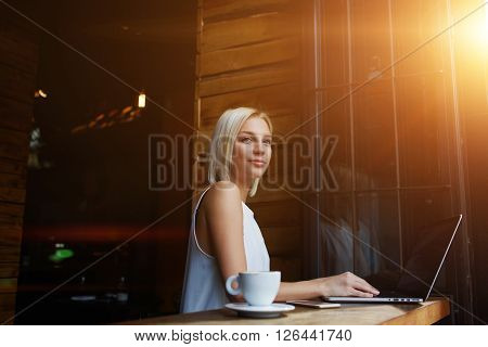 Young charming European woman dreaming about something while sitting with laptop computer in modern coffee shop thoughtful attractive female freelancer using portable net-book for distance work