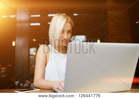Young charming European woman keyboarding on portable net-book during morning breakfast in coffee shop beautiful blonde female student working on laptop computer before her lectures in University