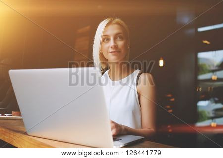 Young gorgeous woman with pretty face working on laptop computer while sitting in modern coffee shop interior charming dreamy European female using portable net-book during recreation time in cafe
