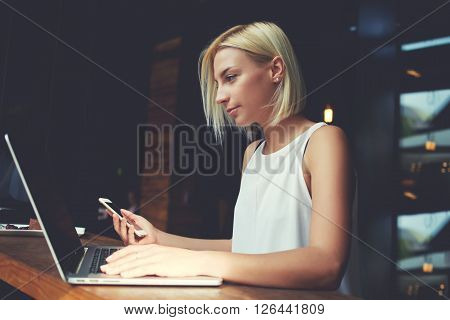 Charming Caucasian woman using mobile phone and laptop computer while sitting in modern coffee shop interior young beautiful hipster girl holding cell telephone during work on portable net-book