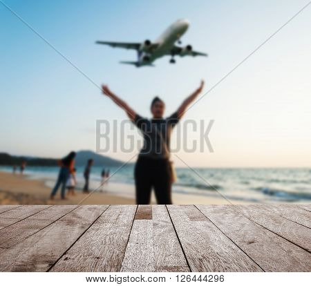 Wooden table top on blurred some people relax on the beach sunset in twilight with plane come in the land Can be used for display or montage your products