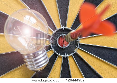 Arrow hitting the bullseye target with idea lamp on dartboard Success business finance investment concept symbol of successful ** Note: Visible grain at 100%, best at smaller sizes