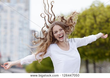 Beautiful young happy smiling woman with hair flying in the sity background