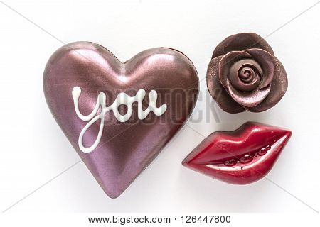 Chocolate heart with word you and chocolate rose with red mouth on white background symbol of love ** Note: Shallow depth of field
