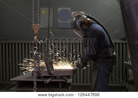 working with a angle grinder in a factory