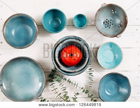 Many turquoise clay empty plates and red decorative ceramic pomegranate  on white wooden background. Flat lay on set of trendy  empty plates and color decor. Organic food, pottery, decoration concept