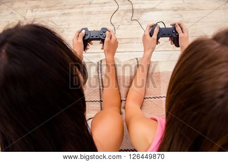 Close Up Portrait Of Two Young Woman Lying With Joysticks