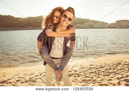 Happy Young Man Piggybacking His Pretty Woman At The Seaside