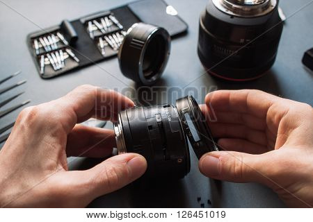 Photo camera lens repair set. Technician engineer disassembling, align and adjusts 50 mm 1.4 photo camera lens. Engineer's hands and maintenance support of broken photographic optic and optical part.
