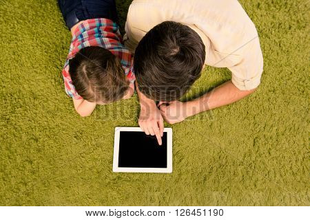 Top View Of Father And Son Lying On Green Carpet With Tablet