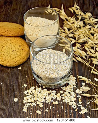 Bran small and flour oat in a two glassful, oatmeal and ears, cookies on a background of wooden boards