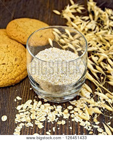 Bran small oat in a two glassful, oatmeal and ears, cookies on a background of wooden boards