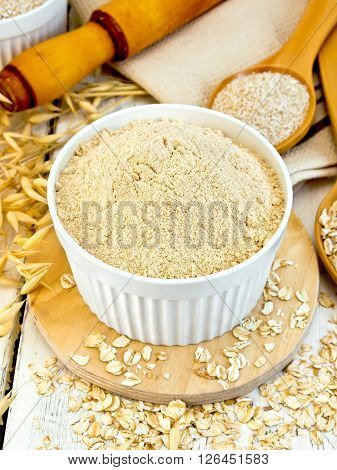 Oat flour in white bowl, oatmeal and bran in a spoon, oat stalks, a rolling pin and a napkin on a wooden boards background