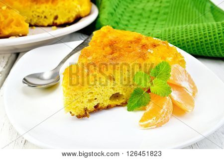 Piece of tart  with mandarin, mint, tangerine slices and spoon in white plate, towel on a background of wooden boards