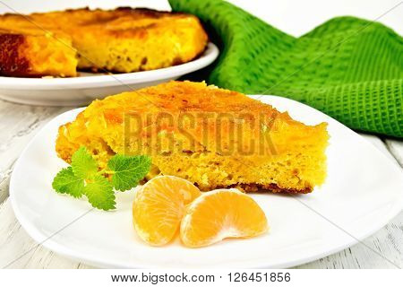 Tart with mandarin, mint, tangerine slices in white plate, a towel on the background light wooden boards