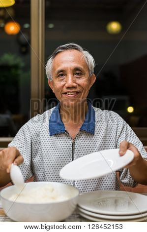 Happy Asian Male Senior Serving Rice