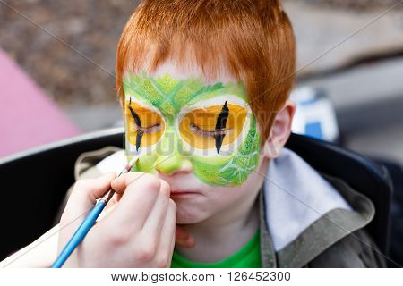Child animator, artist's hand draws face painting to redhead child. Redhead boy with funny face painting. Painter makes reptile eyes at him. Children holiday, event, bithday party, entertainment.