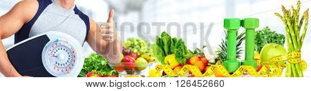 Man with scales over fruits background.