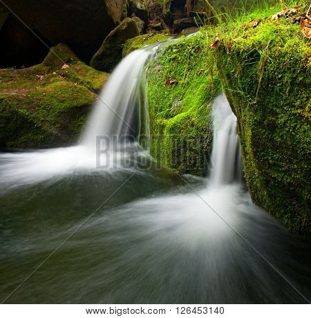 Cascade On Small Mountain Stream. Cold Crystal  Water Is Falling Over Basalt Mossy Boulders Into Sma
