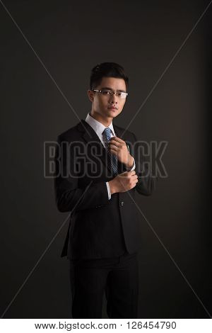 Portrait of Vietnamese business executive buttoning up cuff