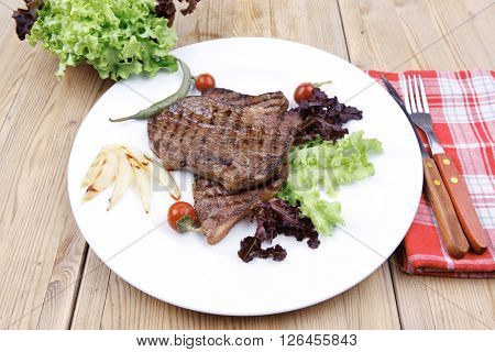 meat food : roast steak boneless with roast onion and red hot peppers, served on green lettuce salad on dish isolated over wooden table