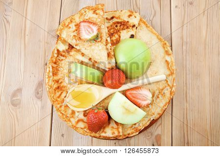 sweet food : big thin pancake with honey strawberries and apple on wooden table