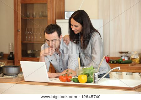 Couple in front laptop computer in the kitchen