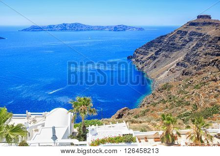 Beautiful typical white greek buildings with different flowers and palm. Sea side of Thira, Santorini island, Greece