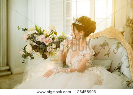 Bride. Wedding. The bride in a short dress with lace in the crown earrings in luxurious interior. Wedding bouquet, makeup, hairstyle. Wedding Style
