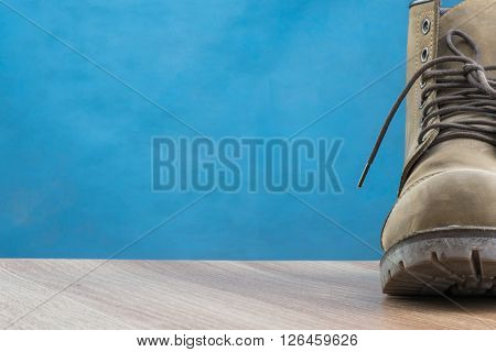 Patina Leather Boot on wooden surface and blue background with space for text